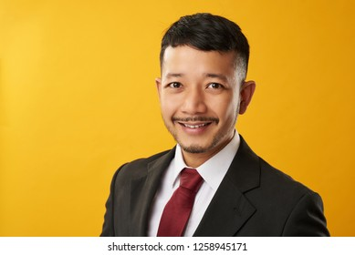 Happy asian guy headshot in color background. Blue neck worker theme