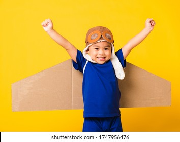 Happy Asian handsome funny child or kid little boy smile wear pilot hat play and goggles raise hand up with toy cardboard airplane wings flying, studio shot isolated yellow background, Startup freedom