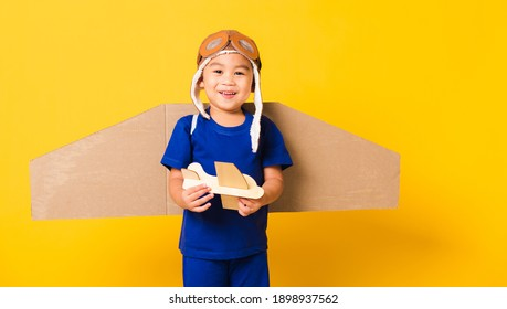 Happy Asian handsome funny child or kid little boy smile wear pilot hat play and goggles with toy cardboard airplane wings fly hold plane toy, studio shot isolated yellow background, Startup freedom