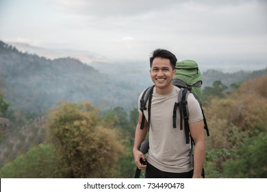 Happy asian hiker. man with backpack hiking in beautiful forest