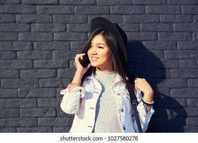 Happy asian hipster girl looking at camera while standing against wall with copy space for advertising. Beautiful young woman talking on mobile phone near stone wall