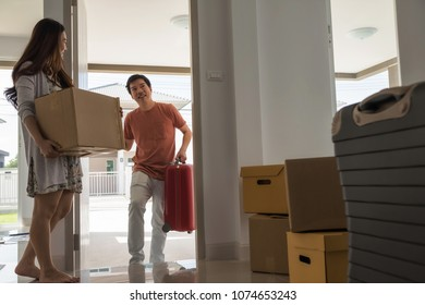 Happy Asian husband carry luggage into new house while female wife carry box and look at her man. moving with many boxes and luggage. First home for new begining couple life.
