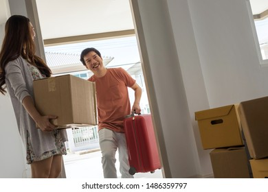 Happy Asian husband carry luggage with smile wife at front door near cardboard box. moving to new home. First house to start couple life. Home leasing or refinance for real estate.