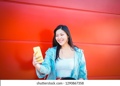 Happy Asian influencer using mobile smart phone outdoor - Chinese fashion girl watching on new trends social networks - Web influencing, millennials, technology and generation z concept