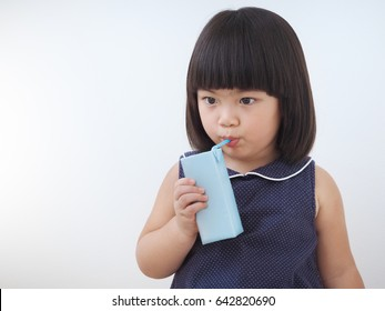 Happy asian kid girl drinking milk from carton box with straw, Blank juice package in hand of healthy child