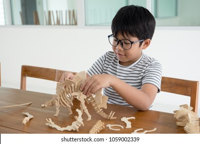 Happy Asian kid on the wood chair enjoy playing 3D dinosour wood toy