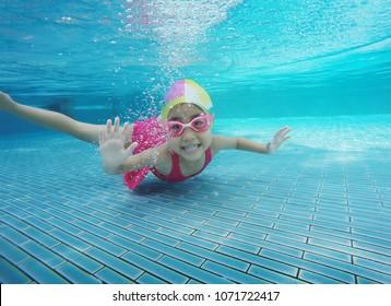 happy asian kid swimming underwater in summer. Outdoor activities in swimming pool.
