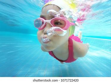 happy asian kid swimming underwater in summer. Outdoor activities in swimming pool. Zoom motion in pool