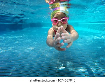happy asian kid swimming underwater in summer. Outdoor activities in swimming pool. Zoom motion in pool