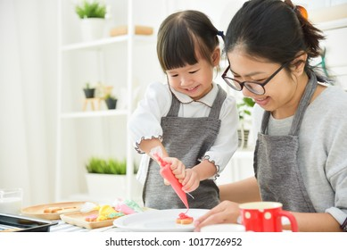 Happy Asian Kid and young mother decorating cookies in the kitchen.
