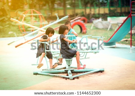9abab51ea Happy Asian kids playing carousel in playground of school. It playtime for  children to playful