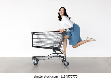 happy asian lady in shopping action with shopping cart on white background.