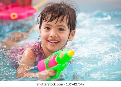 Happy asian little child girl having fun to play water gun and swimming in the pool  in Songkran festival Thailand
