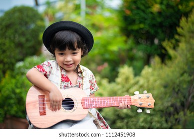 Happy Asian little child girl playing guitar or ukulele in the garden. Music,musician and guitarist concept.(Soft and selective focus)