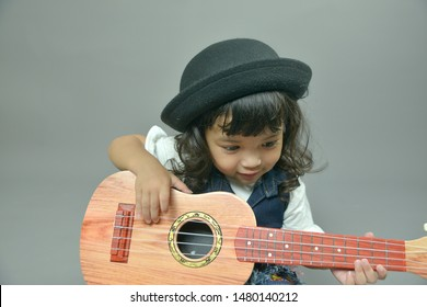 Happy Asian little child girl playing guitar or ukulele isolated on gray background. Music, Musician and guitarist concept.