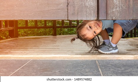 Happy Asian little child girl plays peekaboo under the wooden door in the garden.
