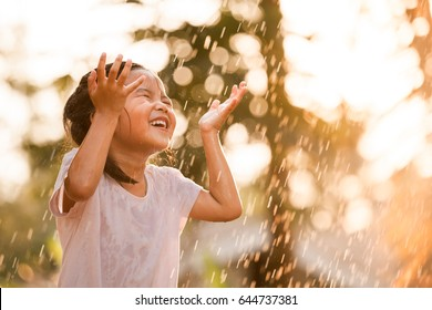 Happy asian little child girl having fun to play with the rain in the evening sunlight in vintage color tone - Shutterstock ID 644737381