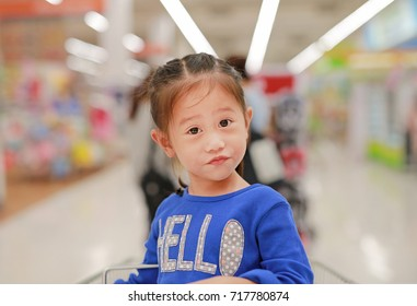Happy Asian little child girl sitting in the trolley during family shopping in the market.