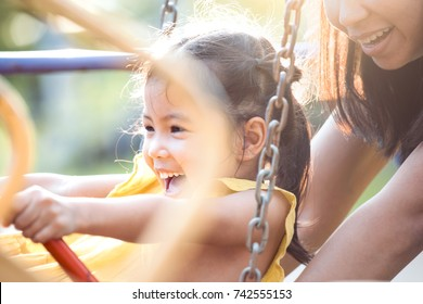 Happy asian little child girl having fun to ride on swings when mother pushing her swings in playground in the sunset time
