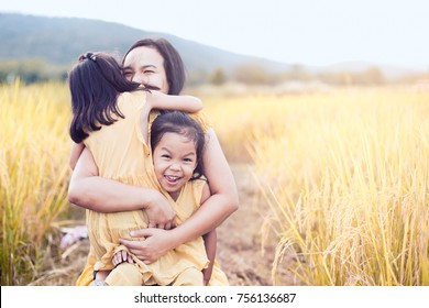 Happy asian little child girls hugging mother and having fun to play with mother in the paddy field in vintage color tone