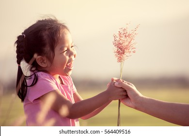 Happy asian little girl giving grass flower to her mother with love in vintage color tone