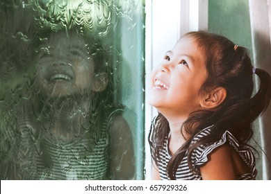 Happy asian little girl looking outside through the window in the rainy day in vintage color tone