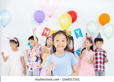 Happy asian little girl in party hat standing with her friend to join birthday party.