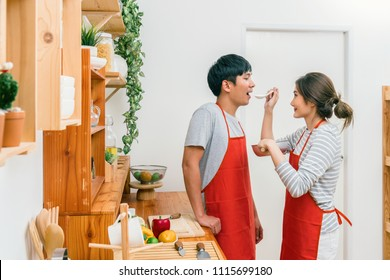 Happy Asian Lover or couple cooking in happiness action in the kitchen room at the modern house, Couple and life style concept.