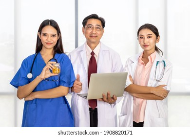 Happy Asian male and female medical doctor team standing and meeting discuss about medicine with laptop computer