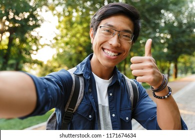 Happy asian male student in eyeglasses making selfie and showing thumb up while looking at the camera outdoors