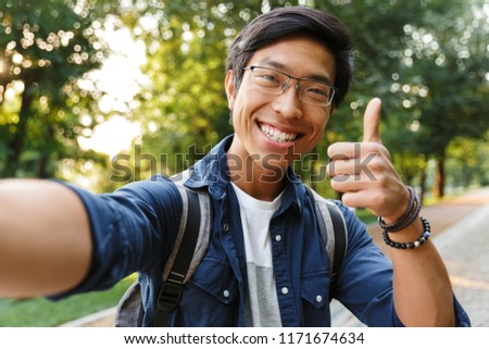 99744e31594d Happy asian male student in eyeglasses making selfie and showing thumb up  while looking at the