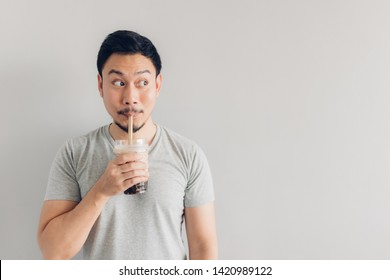 Happy Asian man is drinking Bubble Milk Tea or Pearl Milk Tea. Popular Milk Tea in Asia and Taiwan.