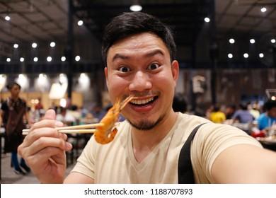 Happy Asian man eat grilled shrimp with chopsticks.