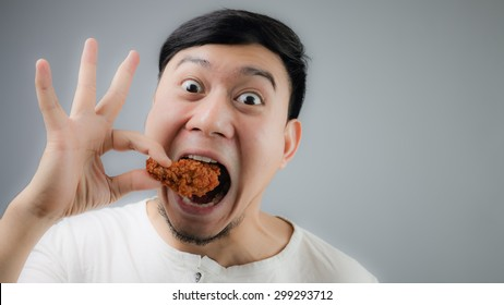 Happy Asian man with fried chicken on grey background.