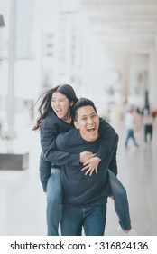 Happy Asian man giving his girlfriend piggy back out door in city and laughing together