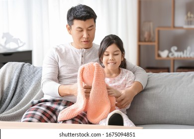 Happy Asian man and his little daughter playing at home