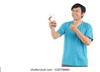 happy asian man holding phone happy with gesture hand thumb ok using blue t-shirt. portrait filipino hand thumb ok with smartphone