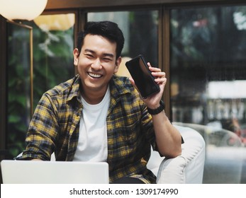 Happy Asian man holding smart phone in hand.