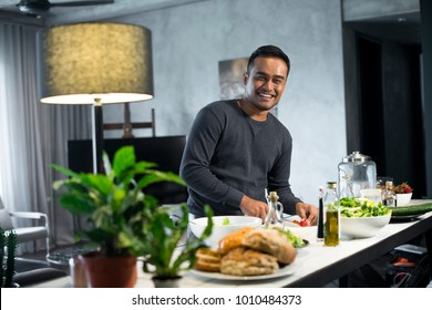 Happy Asian man preparing food in the kitchen at home.