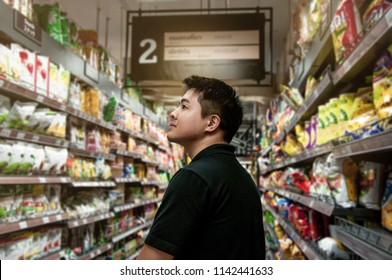 Happy asian man shopping in supermarket, A man looking for some snack from snack zone in supermarket, Young man shopping in  a store, Steward shopping alone, Choosing food in market