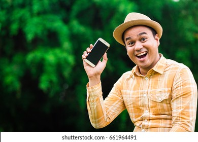 Happy asian man showing smartphone
