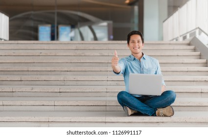 Happy Asian man showing thumb up to celebrate success or achievement while using laptop