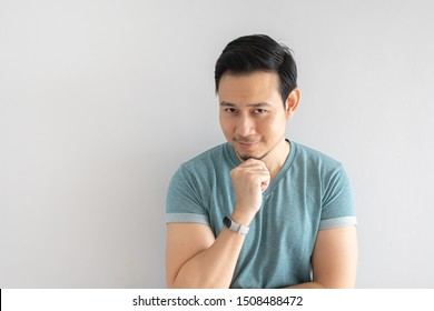 Happy Asian man is smiling with hidden motive face on grey background.