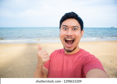 Happy Asian man is taking selfie photo of himself on the beach.