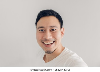 Happy Asian man is taking selfie of himself and present the empty copy space background.