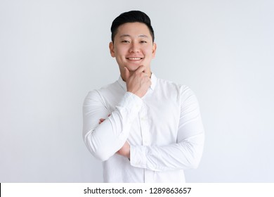 Happy Asian man touching chin and looking at camera. Positive handsome guy standing and posing. Asian man portrait concept. Isolated front view on white background.