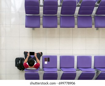Happy Asian man traveler working with technology tablet with suitcase,  smart mobile phone and passport at the seat while waiting airplane depart at the airport, freelance and travel concept