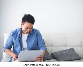 Happy Asian man using laptop in living room.