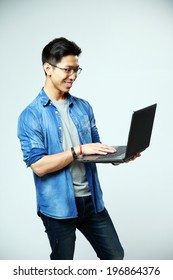 Happy asian man using laptop on gray background