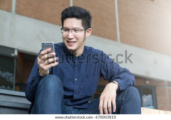 Happy asian man using mobile phone and sitting for checking email. Concept of young people working with mobile devices.